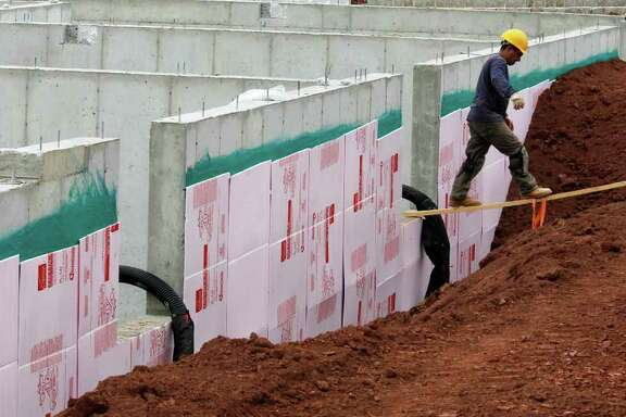 In this Sept. 2, 2011 photo, builders work at a home site in Media, Pa., for K. Hovnanian. Fixed mortgage rates fell this week to the lowest levels in six decades. But few Americans can take advantage of the rates to refinance or buy a home. (AP Photo/Alex Brandon)