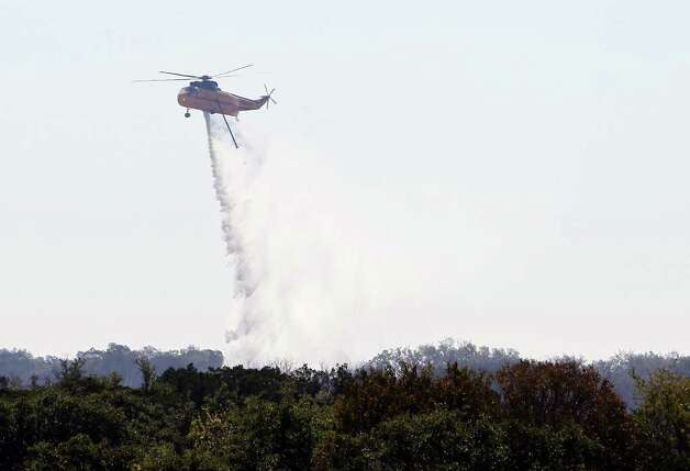 A helicopter drops water on hot spots inside Camp Bullis area on Thursday, Sept. 8, 2011 the day after a 150-acre wildfire burned through the area. Crews were still on hand to knock out any hot spots throughout the day. Kin Man Hui/kmhui@express-news.net Photo: Kin Man Hui, -- / San Antonio Express-News