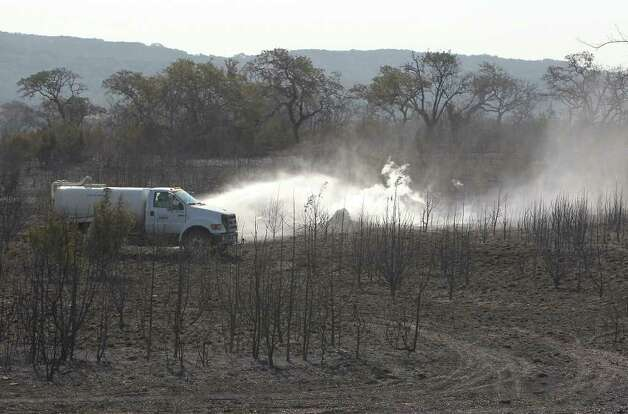 A truck sprays water onto a smoldering pile of earth amongst scorched trees and land inside Camp Bullis area on Thursday, Sept. 8, 2011 the day after a 150-acre wildfire burned through the area. Crews were still on hand to knock out any hot spots throughout the day. Kin Man Hui/kmhui@express-news.net Photo: Kin Man Hui, -- / San Antonio Express-News