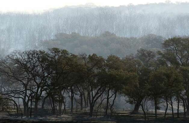Scorched trees and land inside Camp Bullis area on Thursday, Sept. 8, 2011 the day after a 150-acre wildfire burned through the area. Crews were still on hand to knock out any hot spots throughout the day. Kin Man Hui/kmhui@express-news.net Photo: Kin Man Hui, -- / San Antonio Express-News