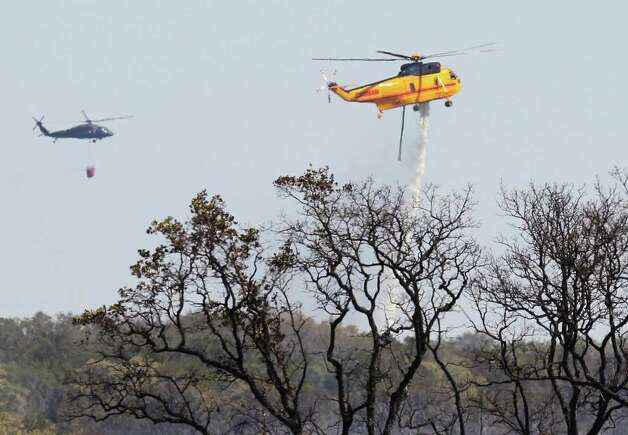 Helicopters drop water on scorched trees and land inside Camp Bullis area on Thursday, Sept. 8, 2011 the day after a 150-acre wildfire burned through the area. Crews were still on hand to knock out any hot spots throughout the day. Kin Man Hui/kmhui@express-news.net Photo: Kin Man Hui, -- / San Antonio Express-News