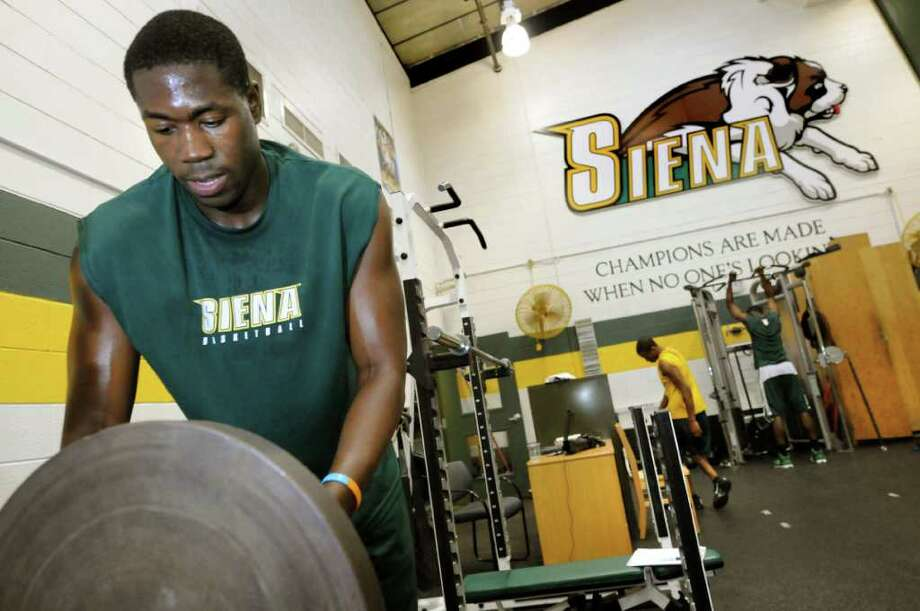 Siena basketball freshman Lionel Gomis adds weight to lift as he works with strength coach Dan Taylor on Friday, June 24, 2011, at Siena College in Loudenville, N.Y. (Cindy Schultz / Times Union) Photo: Cindy Schultz / 00013691A