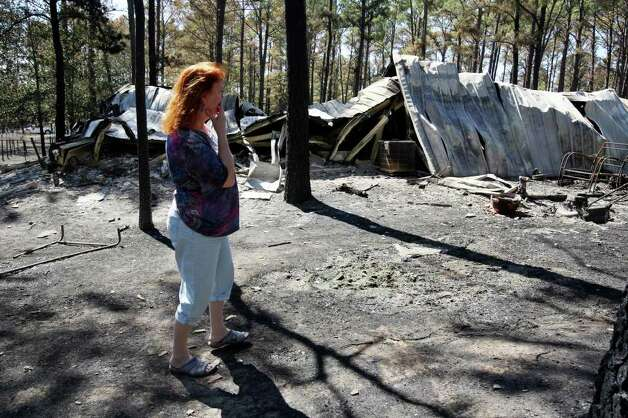 Wanda Cox, 65, looks over her destroyed house in the Circle D subdivision after residents were allowed to return on Thursday, Sept. 8, 2011. Cox and her husband, Randy Powell, saw their address posted on a list of destroyed homes yesterday. Photo: Jerry Lara/glara@express-news.net / SAN ANTONIO EXPRESS-NEWS