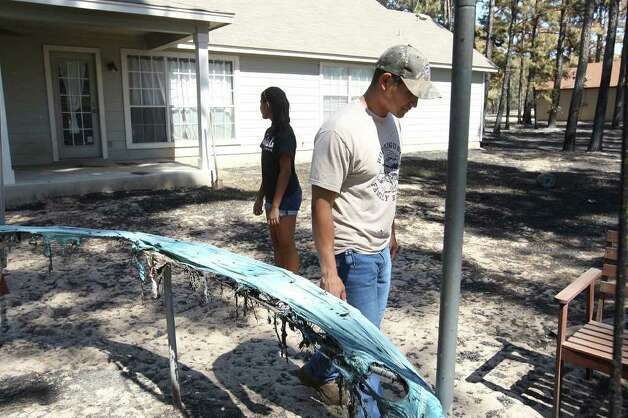 Jaime Gonzales and his daughter, Alexis, inspect damage to their property in the Circle Dsubdivision in Bastrop County on Thursday, Sept. 8, 2011. Residents were allowed to return to certain parts of the wildfire-affected areas of the county that afternoon. Photo: Jerry Lara/glara@express-news.net / SAN ANTONIO EXPRESS-NEWS