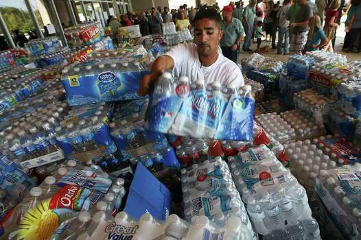 Jason Alfaro arranges donated water as residents gather at the convention center in Bastrop on Thursday, Sept. 8, 2011 to find out the latest news on the wildfires affecting the area. Photo: Jerry Lara/glara@express-news.net / SAN ANTONIO EXPRESS-NEWS