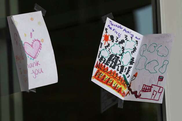Children's drawing are taped to the entrance of the Convention Center in Bastrop as citizen gather Thursday, Sept. 8, 2011 to find out the latest news on the wildfires affecting the area. Photo: Jerry Lara/glara@express-news.net / SAN ANTONIO EXPRESS-NEWS