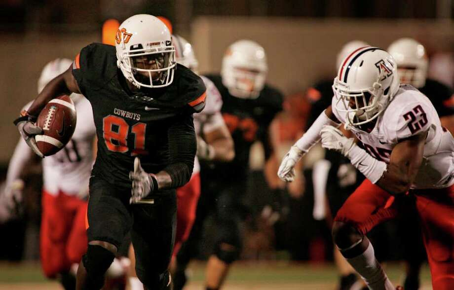 Oklahoma State wide receiver Justin Blackmon (81) slips past Arizona safety Mark Watley during the second half of Thursday's game in Stillwater, Okla. Photo: Brett Deering, Getty / 2011 Getty Images