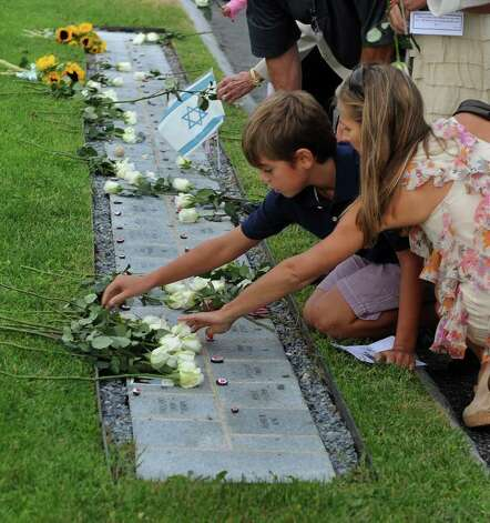 Nicolas Pelletier, 10, and his mom Jacque, of Greenwich, place white roses at the memorial in memory of father and husband Mike who died on 9/11, during Connecticut Remembers: September 11th Memorial Service at Sherwood Island State Park in Westport, Conn. on Thursday September 8, 2011. Photo: Christian Abraham / Co