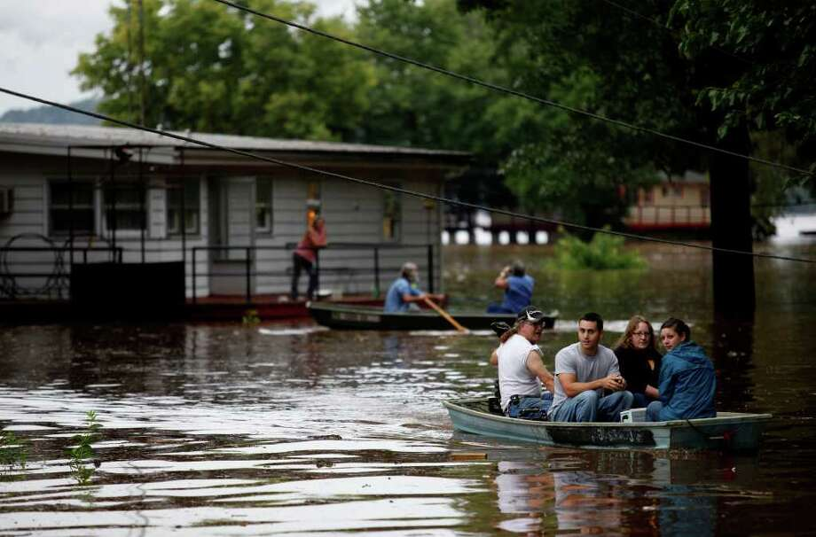 Rich McDave, Chad Bowman, Deb Bowman, and Rebecca Cummins ride out in a motorboat after helping Rob Jackson remove valuables from his deceased parents' home in Goldsboro, Pa., Thursday, Sept. 8, 2011. Days of rainfall from what had been Tropical Storm Lee inundated a wide portion of Pennsylvania and other northeastern states this week, forcing tens of thousands of people to seek higher ground, while pouring into basements and low-lying homes, leaving at least four dead and triggering fears about the adequacy of flood control systems. Photo: Chris Dunn, AP / York Daily Record