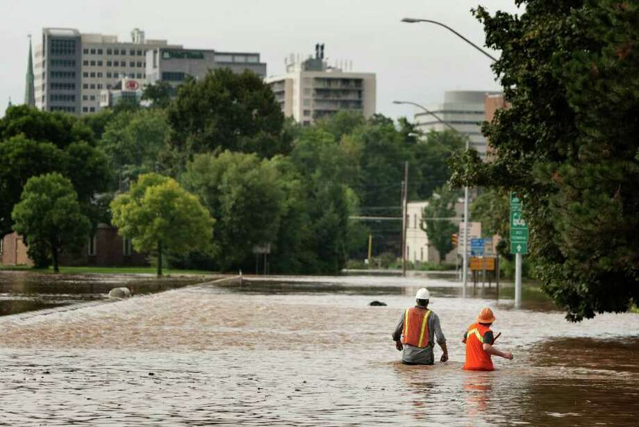 Amtrak workers Nathan Sutton and Robbie Grogan walk toward Harrisburg, Pa.  on the Second Street ramp off of Rt. 83 after setting switches along the tracks  on Thursday Sept. 8, 2011.   Nearly 100,000 people from New York to Maryland were ordered to flee the rising Susquehanna River on Thursday as the remnants of Tropical Storm Lee dumped more rain across the Northeast, closing major highways and socking areas still recovering from Hurricane Irene. Photo: SEAN SIMMERS, AP / PATRIOT-NEWS