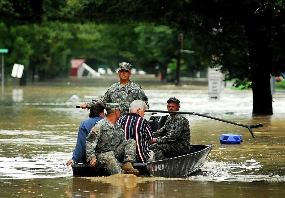 West Pittston Army National Guard rescues residents from their homes in West Pittston, Pa. from flood waters from the Susquehanna River on Thursday, Sept. 8, 2011.  The remnants of Tropical Storm Lee poured water on top of the already soaked Northeast on Thursday, closing hundreds of roads and forcing evacuation orders for more than 100,000 people from the Susquehanna River's worst flooding in nearly 40 years.   (AP Photo/Ralph Francello/THE CITIZENS' VOICE). Photo: Ralph Francello, AP / The Citizens' Voice