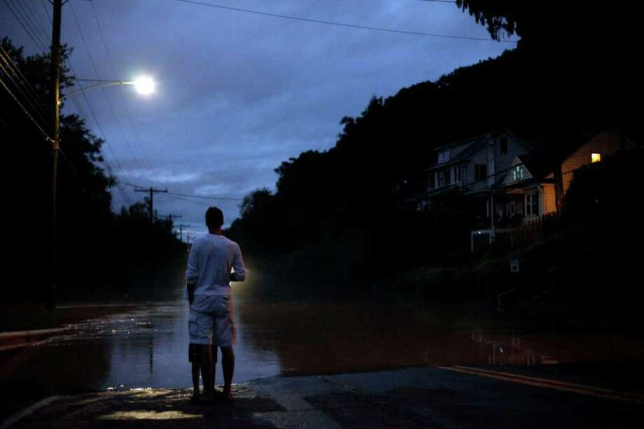 Daryl Kurkoski and his daughter Jennifer, 9, view rising floodwaters, Thursday, Sept. 8, 2011, in Plymouth, Pa. Widespread flooding brought on by the remnants of Tropical Storm Lee was being blamed for two deaths in Pennsylvania, where inundated communities were evacuated and state offices closed down on Thursday because of the rising waters. Photo: Matt Rourke, AP / AP