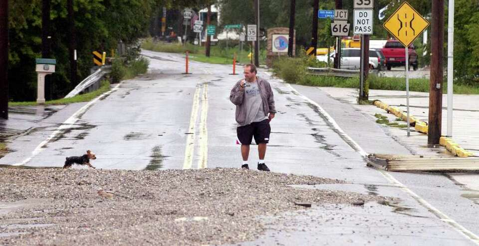 David Sams and his dog, Pepper, walk through the stones along a flooded road in York, Pa.,Thursday,