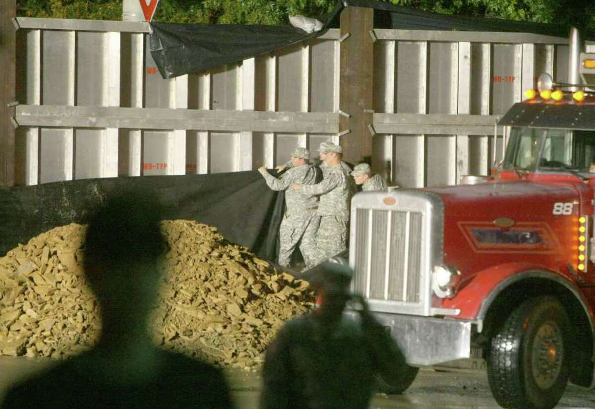 National Guardsmen place mesh tarping and loads of dirt and other materials on the Market Street Bridge flood gate in an effort to stop water that is pouring from the gate's cracks in Wilkes-Barre, Pa., on Thursday Sept. 8, 2011. Nearly 100,000 people from New York to Maryland were ordered to flee the rising Susquehanna River on Thursday as the remnants of Tropical Storm Lee dumped more rain across the Northeast, closing major highways and socking areas still recovering from Hurricane Irene.