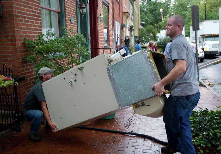 John Depuy left, and Dan Robinson of H.L. Bowman remove a gas fired furnace from a home in Shipoke , Pa. Thursday Sept. 8, 2011.   Nearly 100,000 people from New York to Maryland were ordered to flee the rising Susquehanna River on Thursday as the remnants of Tropical Storm Lee dumped more rain across the Northeast, closing major highways and socking areas still recovering from Hurricane Irene. Photo: John C. Whitehead, AP / THE PATRIOT-NEWS