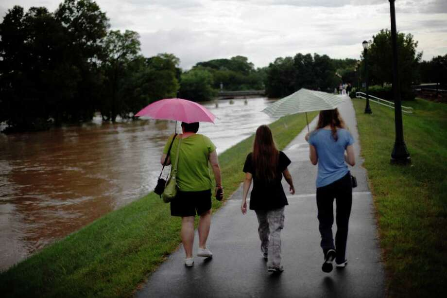 People walk on the levee next to the swollen Susquehanna River, Thursday, Sept. 8, 2011, in Kingston, Pa. Widespread flooding brought on by the remnants of Tropical Storm Lee was being blamed for two deaths in Pennsylvania, where inundated communities were evacuated and state offices closed down on Thursday because of the rising waters. Photo: Matt Rourke, AP / AP