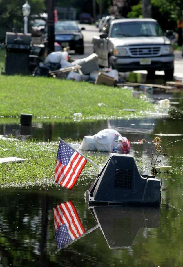 A U.S. flag clipped to a television set sits  in floodwaters from  the effects of Tropical Storm Lee, Thursday, Sept. 8, 2011, in Pompton Lakes, N.J.  Nearly 100,000 people from New York to Maryland were ordered to flee the rising Susquehanna River on Thursday as the remnants of Tropical Storm Lee dumped more rain across the Northeast, closing major highways and socking areas still recovering from Hurricane Irene. Photo: Julio Cortez, AP / AP