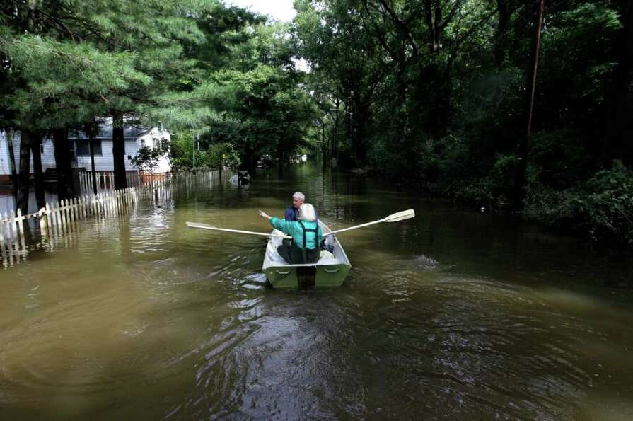 A couple paddle through floodwaters on Lincoln Boulevard in Lincoln Park, N.J., where the Passaic Ri