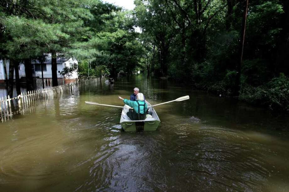 A couple paddle through floodwaters on Lincoln Boulevard in Lincoln Park, N.J., where the Passaic River neared its cresting point, Thursday, Sept. 8, 2011. The couple, who evacuated the area, were on their way to check on their pets which they left behind at the house. Forecasters say New Jersey's streams and rivers remain at or in flood stage with remnants of Tropical Storm Lee bringing more rain to the area. Photo: Julio Cortez, AP / AP
