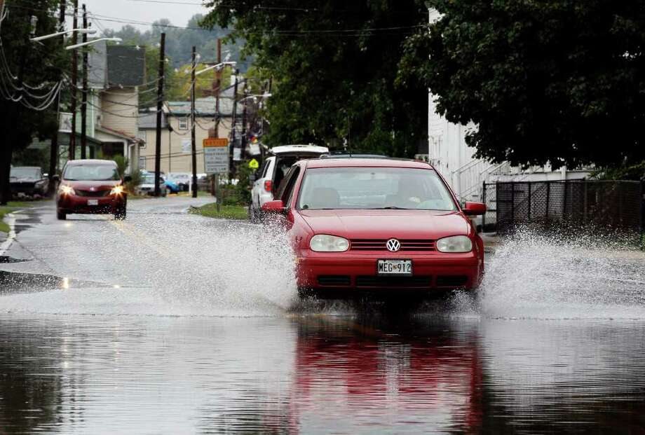 A car makes its way across a flooded street in Port Deposit, Md., Thursday, Sept. 8, 2011, where rainfall from the remnants of Tropical Storm Lee is expected to cause more flooding. The National Weather Service predicted rain would continue to fall heavily across the mid-Atlantic and Northeastern states through Thursday with anywhere from 4 to 7 more inches falling and up to 10 inches in isolated pockets. Flood watches and warnings were in effect from Maryland to New England. Photo: Patrick Semansky, AP / AP