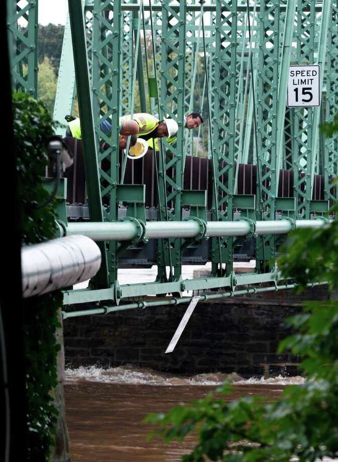 Officials look from the Lambertville-New Hope, Pa., bridge  Thursday, Sept. 8, 2011, in Lambertville, N.J., at the rain swollen Delaware River, as they examine the bridge which was closed earlier Thursday. Remnants from tropical Storm Lee continue to produce heavy rain that could force flood-weary New Jerseyans to head for higher ground Thursday. Photo: Mel Evans, AP / AP
