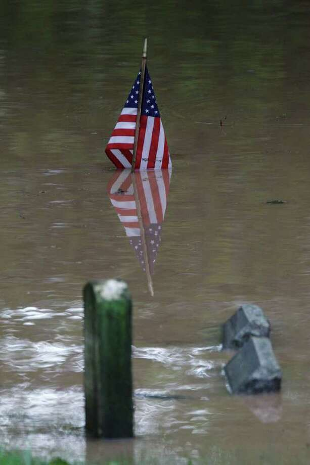 A flag stands in a flooded section of a cemetery, Thursday, Sept. 8, 2011, in Wilkes-Barre, Pa. Widespread flooding brought on by the remnants of Tropical Storm Lee was being blamed for two deaths in Pennsylvania, where inundated communities were evacuated and state offices closed down on Thursday because of the rising waters. Photo: Matt Rourke, AP / AP