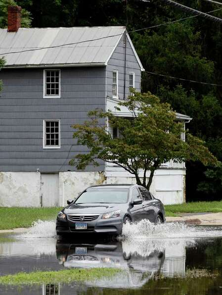 A car crossesa flooded street in Port Deposit, Md., Thursday, Sept. 8, 2011, where rainfall from the