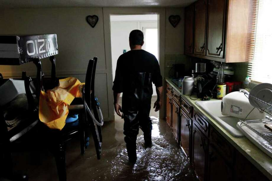 Mario Ortiz, walks through floodwaters in his kitchen Thursday, Sept. 8, 2011, in Wilkes-Barre, Pa. Widespread flooding brought on by the remnants of Tropical Storm Lee was being blamed for two deaths in Pennsylvania, where inundated communities were evacuated and state offices closed down on Thursday because of the rising waters. Photo: Matt Rourke, AP / AP