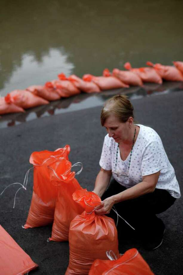 Mary Evans ties sandbags that will be placed in hopes of holding back floodwaters from her home Thursday, Sept. 8, 2011, in Wilkes-Barre, Pa. Widespread flooding brought on by the remnants of Tropical Storm Lee was being blamed for two deaths in Pennsylvania, where inundated communities were evacuated and state offices closed down on Thursday because of the rising waters. Photo: Matt Rourke, AP / AP