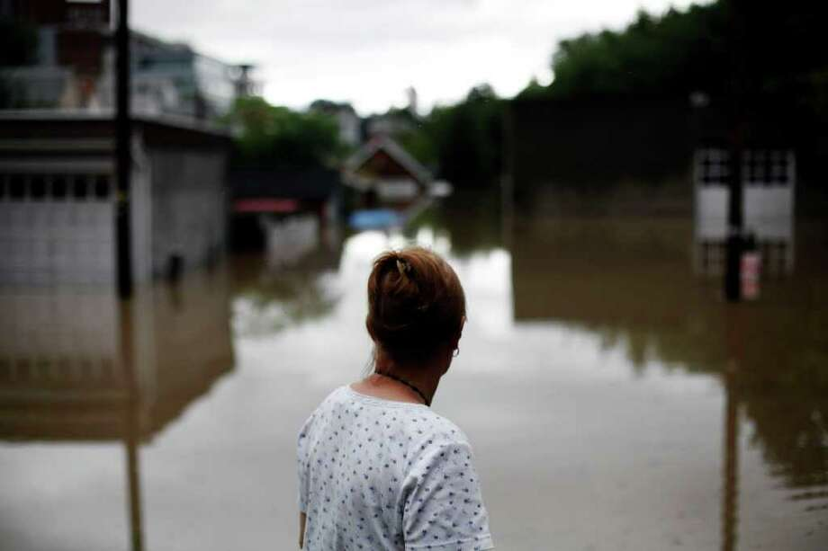 Mary Evans looks out at floodwaters near her home Thursday, Sept. 8, 2011, in Wilkes-Barre, Pa. Widespread flooding brought on by the remnants of Tropical Storm Lee was being blamed for two deaths in Pennsylvania, where inundated communities were evacuated and state offices closed down on Thursday because of the rising waters. Photo: Matt Rourke, AP / AP
