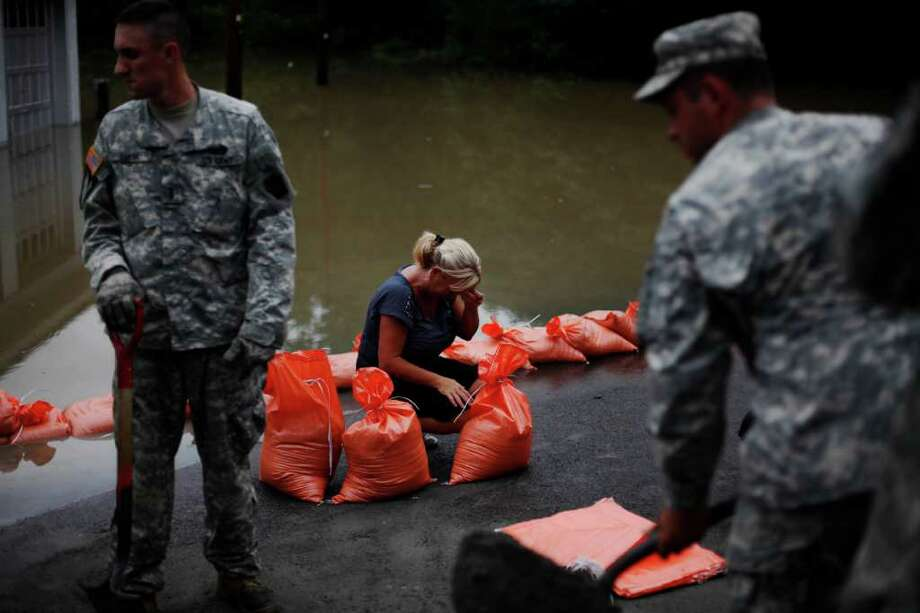 Elaine Delzeit, center, as she ties  sandbags next to rising floodwaters, Thursday, Sept. 8, 2011, in Wilkes-Barre, Pa. Widespread flooding brought on by the remnants of Tropical Storm Lee was being blamed for two deaths in Pennsylvania, where inundated communities were evacuated and state offices closed down on Thursday because of the rising waters. Photo: Matt Rourke, AP / AP