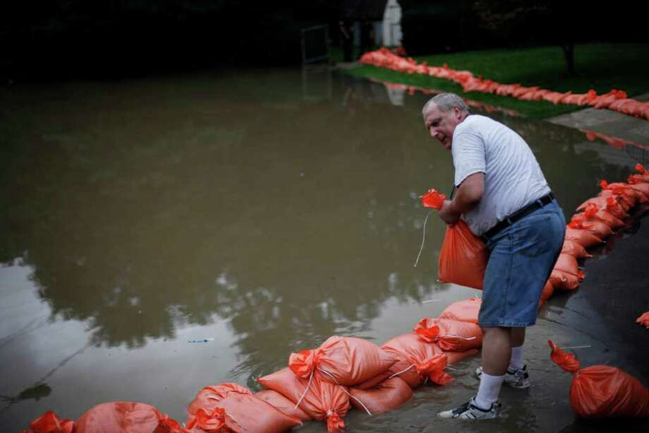 Bob Meluskey, places a sandbag as floodwaters rise Thursday, Sept. 8, 2011, Wilkes-Barre, Pa., in Widespread flooding brought on by the remnants of Tropical Storm Lee was being blamed for two deaths in Pennsylvania, where inundated communities were evacuated and state offices closed down on Thursday because of the rising waters. Photo: Matt Rourke, AP / AP