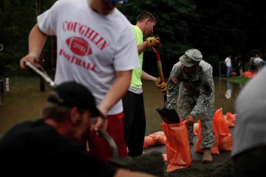 Sgt. Chris Henneforth with the Pennsylvania National Guard, Alpha Company, 1st of the 109th Infantry Regiment out of Honesdale Pa., helps fill sandbags, Thursday, Sept. 8, 2011, in Wilkes-Barre, Pa. Widespread flooding brought on by the remnants of Tropical Storm Lee was being blamed for two deaths in Pennsylvania, where inundated communities were evacuated and state offices closed down on Thursday because of the rising waters. Photo: Matt Rourke, AP / AP