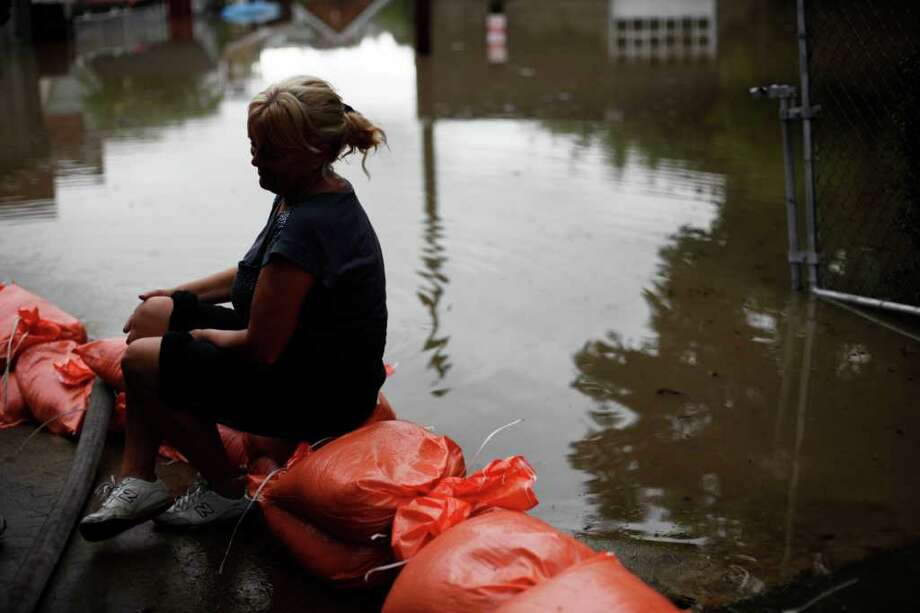 Elaine Delzeit takes a rest on sandbags nest to rising floodwaters, Thursday, Sept. 8, 2011, in Wilkes-Barre, Pa. Widespread flooding brought on by the remnants of Tropical Storm Lee was being blamed for two deaths in Pennsylvania, where inundated communities were evacuated and state offices closed down on Thursday because of the rising waters. Photo: Matt Rourke, AP / AP