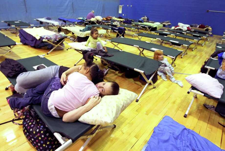 Wilkes-Barre evacuees Kim R. and her daughter Arianna J., 5, rest on their cot at the G.A.R. High School shelter location in Wilkes-Barre, Pa., Thursday, Sept. 8, 2011.  Nearly 100,000 people from New York to Maryland were ordered to flee the rising Susquehanna River on Thursday as the remnants of Tropical Storm Lee dumped more rain across the Northeast, closing major highways and socking areas still recovering from Hurricane Irene. (AP Photo/The Citizens' Voice, Kristen Mullen)  MANDATORY CREDIT Photo: Kristen Mullen, AP / The Citizens' Voice