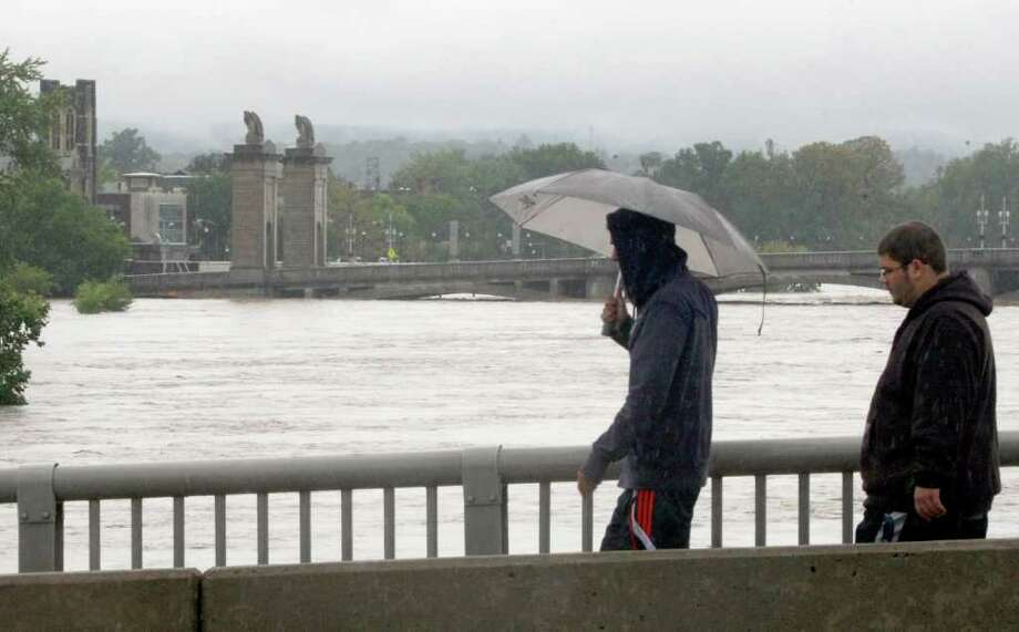 People view the swollen Susquehanna River as they walk across the Pierce Street Bridge in Wilkes-Barre, Pa., Thursday, Sept. 8, 2011.  Nearly 100,000 people from New York to Maryland were ordered to flee the rising Susquehanna River on Thursday as the remnants of Tropical Storm Lee dumped more rain across the Northeast, closing major highways and socking areas still recovering from Hurricane Irene. (AP Photo/The Citizens' Voice, Kristen Mullen)  MANDATORY CREDIT Photo: Kristen Mullen, AP / The Citizens' Voice