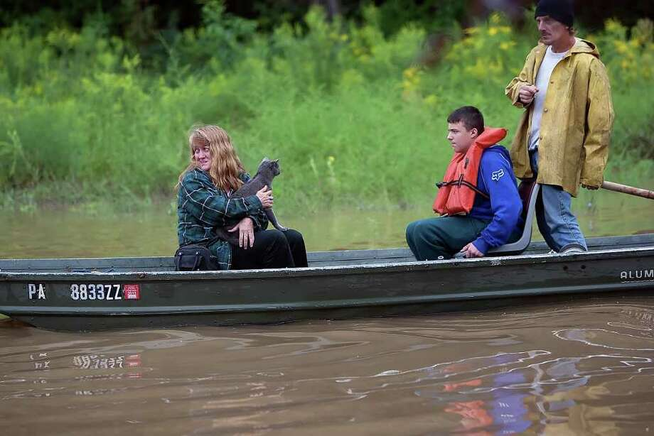 Tami Haynes holds her cat Smokey after rescuing it from her flooded camper  in Middletown, Pa.  on Thursday, Sept. 8, 2011.  Nearly 100,000 people from New York to Maryland were ordered to flee the rising Susquehanna River on Thursday as the remnants of Tropical Storm Lee dumped more rain across the Northeast, closing major highways and socking areas still recovering from Hurricane Irene. Photo: Christine Baker, AP / The Patriot-News