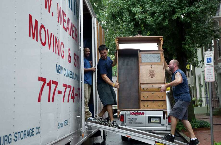 Joe Starry left, and Mark Tadych of Geo W. Weaver Moving & storage help Shipoke, Pa.  remove furniture Thursday Sept. 8, 2011.   Nearly 100,000 people from New York to Maryland were ordered to flee the rising Susquehanna River on Thursday as the remnants of Tropical Storm Lee dumped more rain across the Northeast, closing major highways and socking areas still recovering from Hurricane Irene. Photo: John C. Whitehead, AP / THE PATRIOT-NEWS