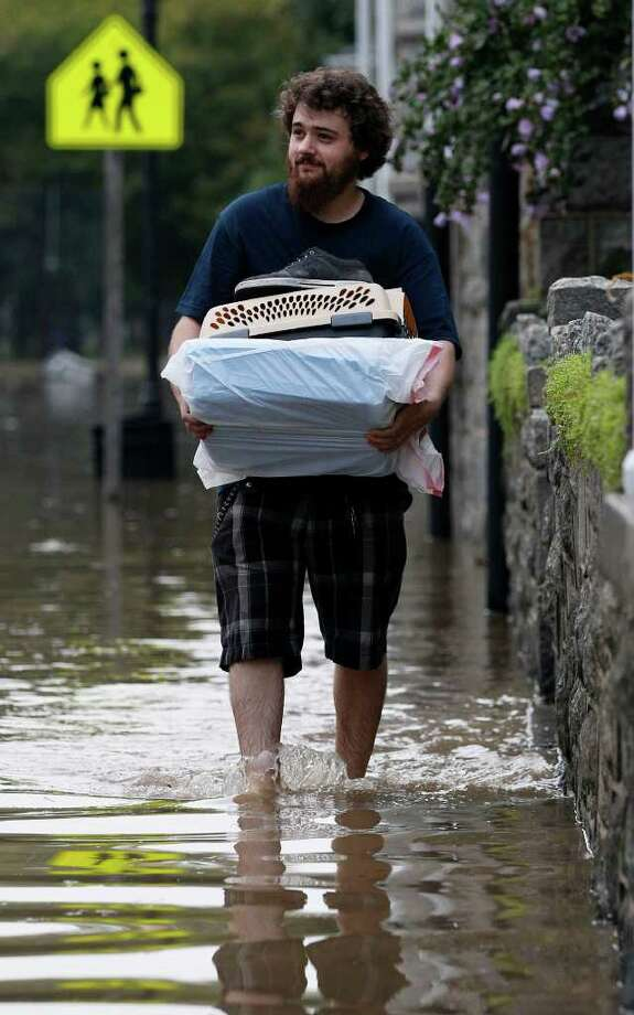 Dustin Campbell evacuates Port Deposit, Md., Thursday, Sept. 8, 2011, as the Susquehanna River, which is swollen with rain from the remnants of Tropical Storm Lee, continues to rise. Photo: Patrick Semansky, AP / AP