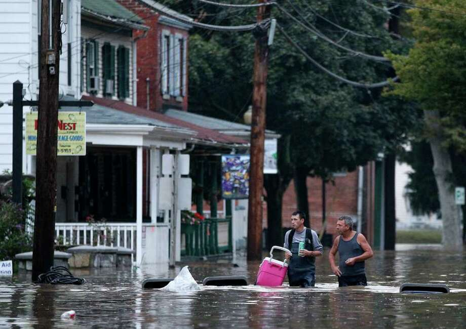 Johnny Bowman, Jr., left, and his father Johnny, Sr., walk down a flooded street in Port Deposit, Md., Thursday, Sept. 8, 2011, as the Susquehanna River, which is swollen with rain from the remnants of Tropical Storm Lee, continues to rise. Johnny, Sr., was helping his son move belongings to an upper floor in his home before evacuating. Photo: Patrick Semansky, AP / AP