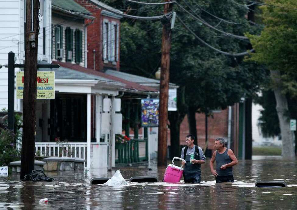 Johnny Bowman, Jr., left, and his father Johnny, Sr., walk down a flooded street in Port Deposit, Md., Thursday, Sept. 8, 2011, as the Susquehanna River, which is swollen with rain from the remnants of Tropical Storm Lee, continues to rise. Johnny, Sr., was helping his son move belongings to an upper floor in his home before evacuating.