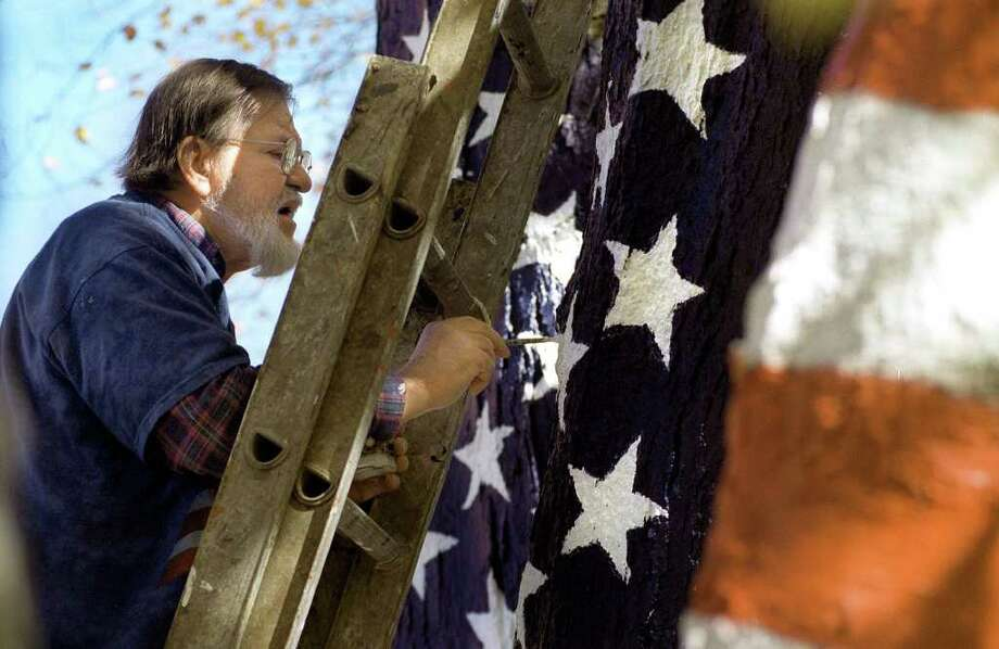 Artist David Merrill of Newtown paints the American flag on tree trunks at the home of Howard Lasher in Newtown in October 2001. Photo: Carol Kaliff / The News-Times