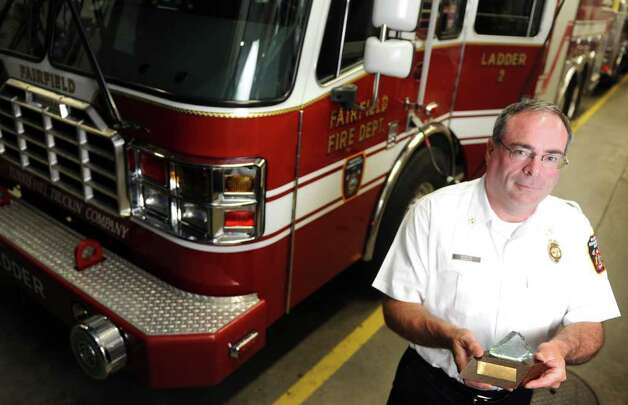 Fairfield Asst. Fire Chief Doug Chavenello holds a shard of glass that he kept from the rubble at ground zero following the attacks of 9/11.  Chavanello was a first responder and spent more than two weeks helping in New York City. Photo: Autumn Driscoll / Connecticut Post