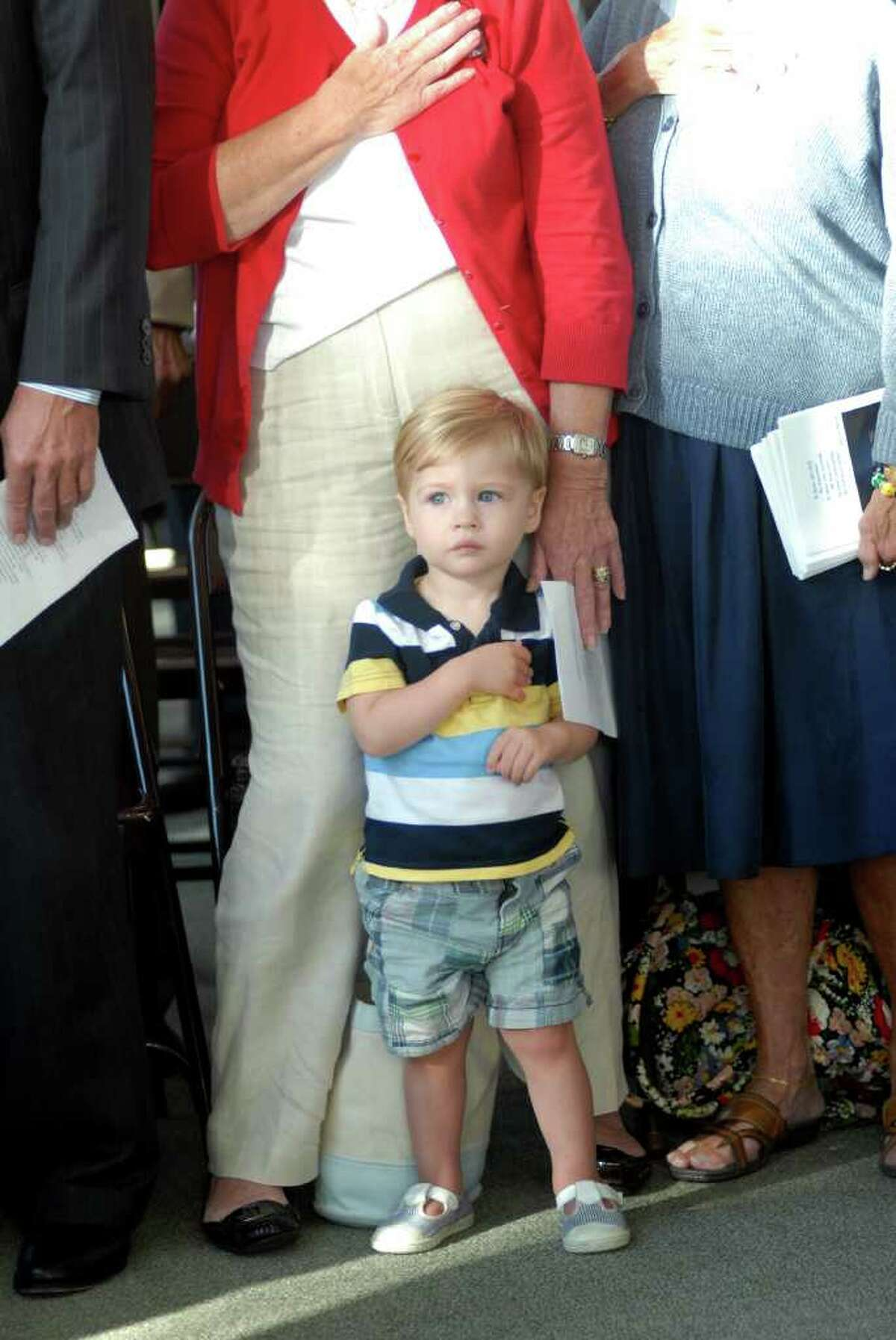 One year old Dean Filippone, grandson of Rep Livvy Floren (149) holds his hand over his heart during the Pledge of Allegiance at 9/11 ceremony at the Government Center in Stamford, Conn. on Friday September 9, 2011 to dedicate a new memorial created from a piece of steel from the Twin Towers.