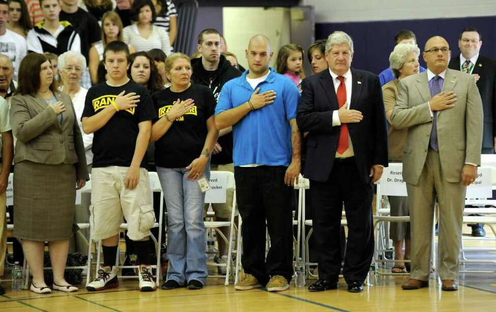 Members of the audience including state Sen. Roy McDonald, second from right, and two honorees hold their hands over their hearts during the Pledge of Allegiance at the 9/11 remembrance assembly at the Ballston Spa High School in Ballston Spa, N.Y., on Sept. 9, 2011. (Skip Dickstein/Times Union)