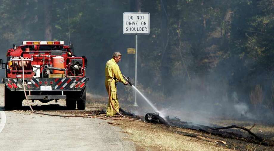 Firefighters put out a fire on FM 1488 and Oakhill in Waller County on Friday. Firefighters  are still trying to contain the Riley Road Fire that's burned more than 8,000 acres and destroyed 70 homes in Waller. Photo: Nick De La Torre, Houston Chronicle / © 2011 Houston Chronicle