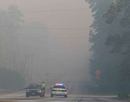 Authorities block smoke-filled FM 1486 in Montgomery County.  Photo: Nick De La Torre, Houston Chronicle / © 2011 Houston Chronicle