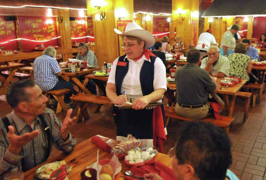 Server Ruby Huntley, clad in cowgirl attire, takes an order during lunch at the Little Red Barn Steakhouse, 1836 Hackberry St. Photo: Photo By Robin Jerstad/Special To The Express-News / Robert Jerstad