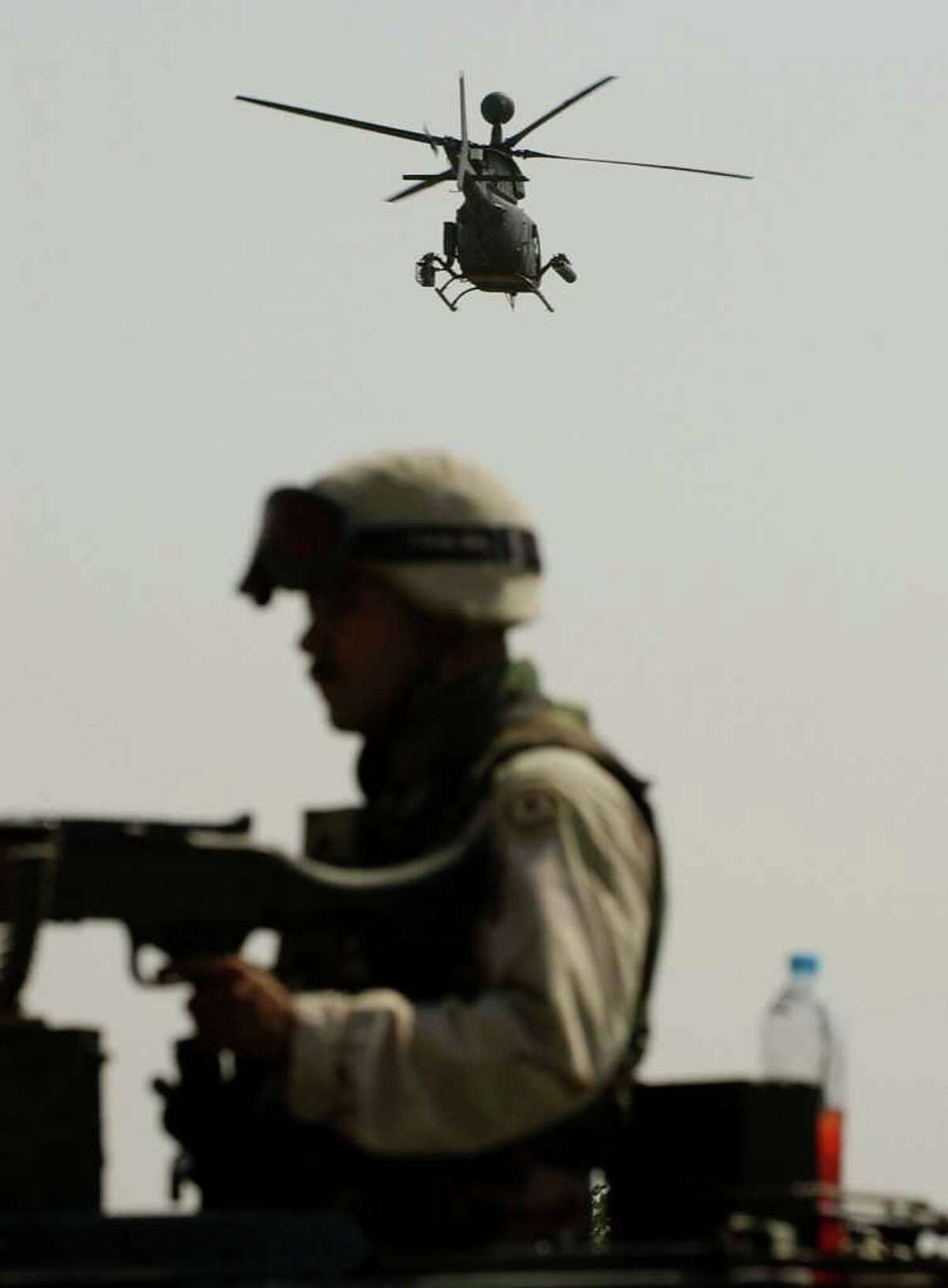STAN HONDA : AFP/GETTY IMAGES AT WAR: A U.S. Army Kiowa reconnaissance helicopter flies over a soldier on a highway just west of Baghdad in Iraq. The invasion toppled the Iraqi president, Saddam Hussein.
