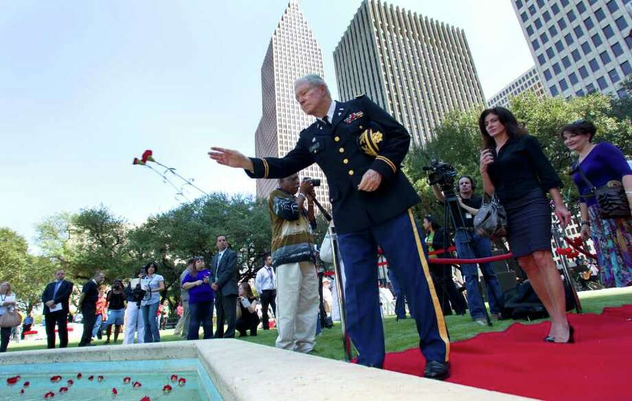 Retired Army chaplain Col. John Price tosses a pair of flowers into the reflecting pond outside City Hall during the city's 9-11 Tenth Anniversary Commemoration in Hermann Square Friday, Sept. 9, 2011, in Houston. Photo: Brett Coomer, Houston Chronicle / © 2011 Houston Chronicle